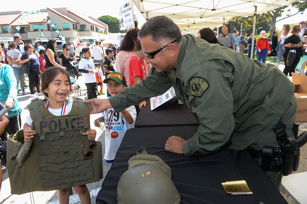 . SWAT Officer Fernando Sanchez has Lourdes Ecute, 8,try on their tactical vest during the Whittier Police Department Open House on Penn Street in Whittier on Saturday May 13, 2017. (Photo by Keith Durflinger/Whittier Daily News/SCNG)