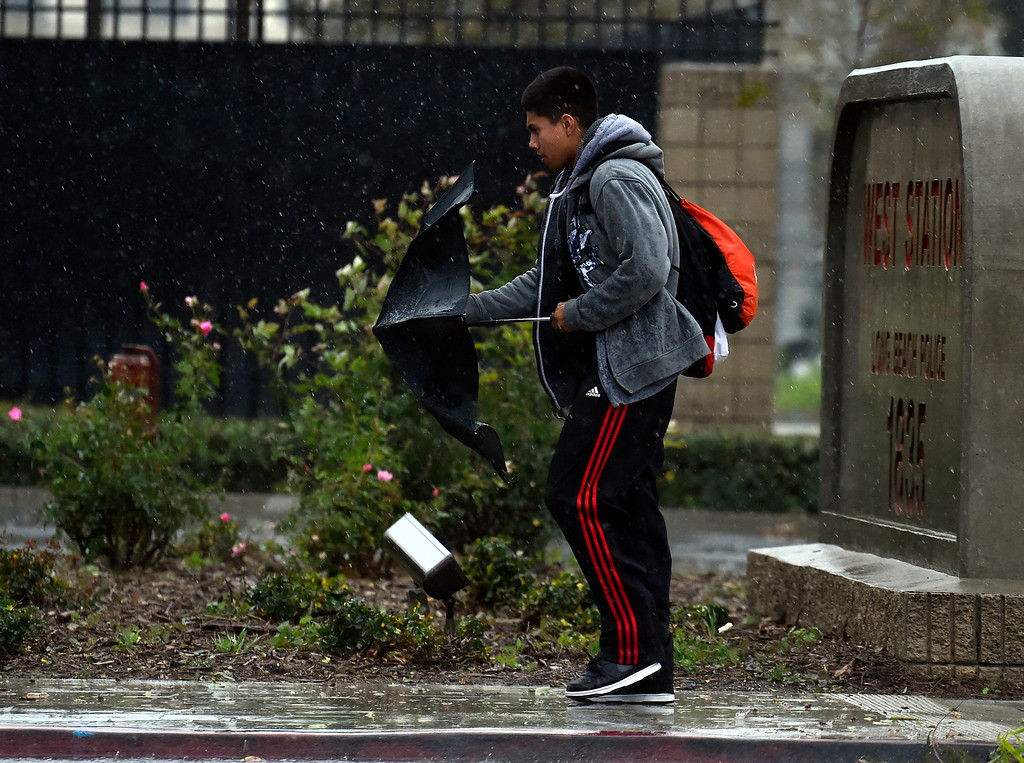 . A student leaving Cabrillo High School struggles with his umbrella in heavy winds and rain in Long Beach, CA on Friday, February 17, 2017. (Photo by Scott Varley, Press-Telegram/SCNG)