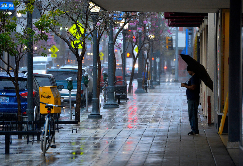 . A man with an umbrella takes shelter from the rain along Pine Avenue in Long Beach, CA on Friday, February 17, 2017. (Photo by Scott Varley, Press-Telegram/SCNG)