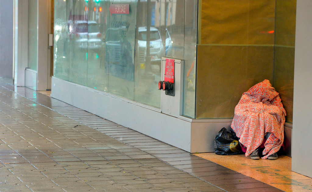 . A person takes shelter from the rain under a blanket in the doorway of a closed store on Pine Avenuein Long Beach, CA on Friday, February 17, 2017. (Photo by Scott Varley, Press-Telegram/SCNG)