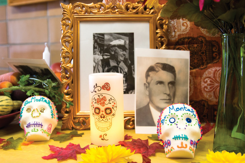 Matthew Gaston | The Sheridan Press<br>Just outide the library at Holy Name Catholic School is an ofrenda, an alter decorated with sugar skulls, flowers and photographs of loved ones who have past away in honor of Dia de los Muertos Wednesday, Oct. 31, 2018. Spanish teacher Maria Montano has encouraged students to bring photos of their loved ones to place on the ofrenda in celebration of the holiday.