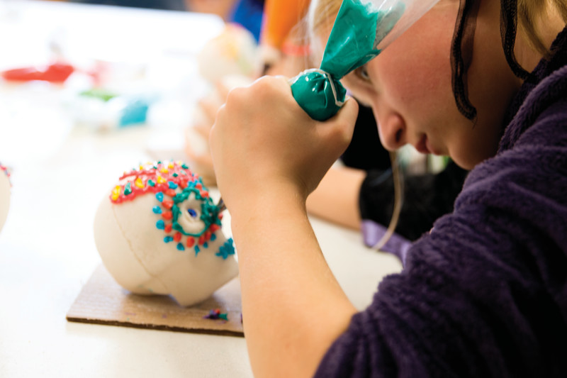 Matthew Gaston | The Sheridan Press<br>Savanah Sutton, a fifth-grader at Holy Name Catholic School, decorates a suger skull for Dia de los Muertos during her Spanish class Wednesday, Oct. 31, 2018.