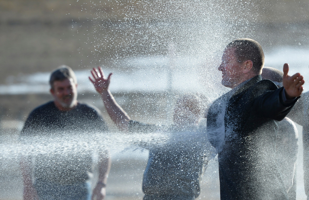 Justin Sheely | The Sheridan Press<br /> Kevin Charlson gets blasted by a fire hose at Woodland Park Elementary School Tuesday, March 20, 2018. Several Woodland Park teachers were sprayed down by a fire hose in celebration of their classrooms raising $80 in a penny drive for the Wyoming Special Olympics.
