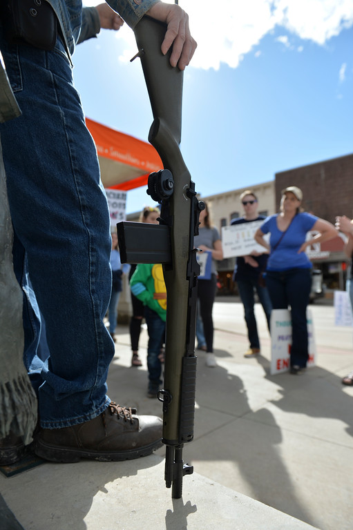 Justin Sheely | The Sheridan Press<br /> David Kuzara leans on his BB gun styled as an M1 rifle during The March for Our Lives demonstration on Main Street in Sheridan Saturday, March 24, 2018. Kuzara argued with the marchers on gun control legislation.