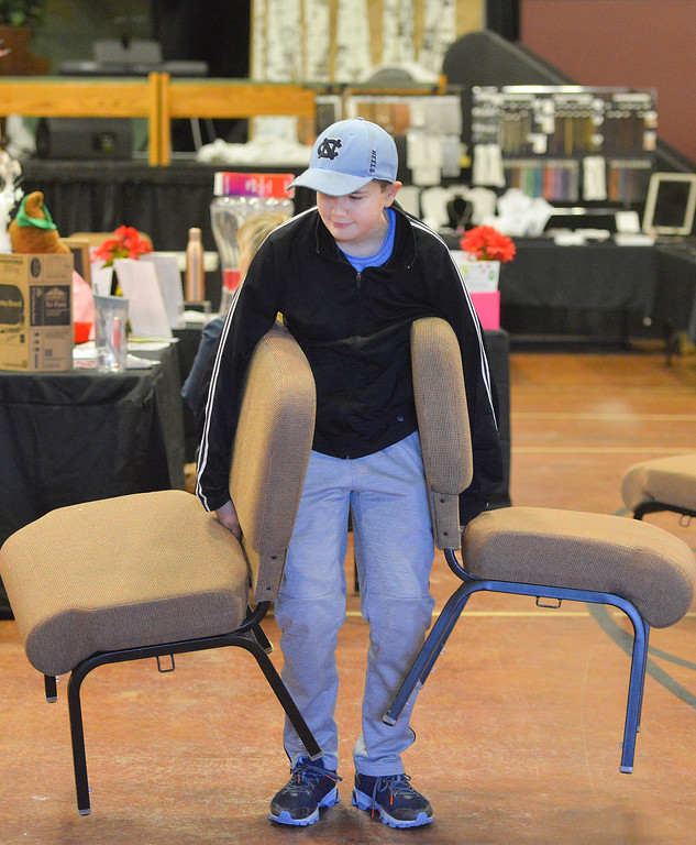 Justin Sheely | The Sheridan Press<br /> Fourteen-year-old Hayden Tellez moves chairs for his family's booth during the Get out and Shop event at Sheridan Wesleyan Church Saturday, March 3, 2018.