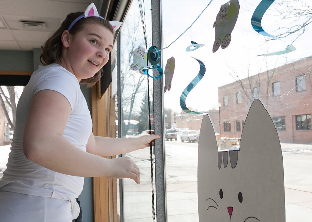 Tibby McDowell | The Sheridan Press<br /> Alora Fields with Girl Scout Troop 6268, eyes the banner she hangs to be sure it's straight while setting up for the Kitten Shower to benefit Second Chance Cat Shelter at the Sheridan Memorial Hospital Community Conference Room Saturday, March 3, 2018.