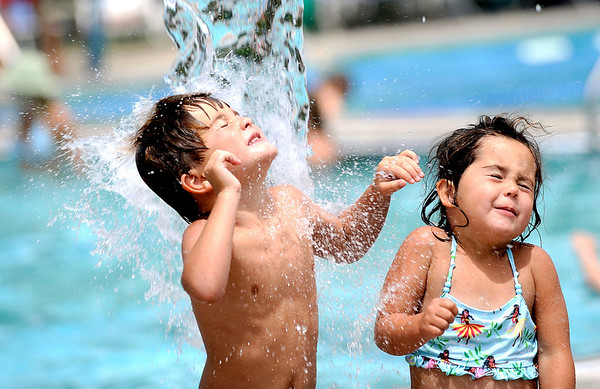 Ethan Johnson (left), 5, and his sister Taylor Johnson (left), 4, close their eyes as water from a bucket splashes on their heads at Spruce Pool in Boulder, Colorado July 13, 2010.  Temperatures in Boulder reached 97 degrees on Tuesday. CAMERA/Mark Leffingwell