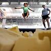 Magnus White (left), 4, leaps in to the foam pit while being watched by his coach, Molly Hooker (right), during gymnastics class at the North Boulder Recreation Center in Boulder, Colorado August 4, 2010.  CAMERA/Mark Leffingwell