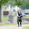 Don Knight | The Herald Bulletin<br /> A lone bagpiper walks toward Howard Martin's burial site  at the Elwood Cemetery on Saturday. Hundreds turned out to show their respect.