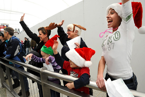 """DIA02.JPG DIA<br /> Left to right, Kristine Cline and Sally Stearns, along with Cline's children Madysen, Mark and Macayla,(far right) jump and wave as they spot their relative arriving at Denver International Airport on Wednesday morning. For a video of DIA, visit  <a href=""""http://www.dailycamera.com"""">http://www.dailycamera.com</a>.<br /> <br /> Photo by Marty Caivano/Dec. 22, 2010"""