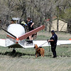 PLANE02.JPG PLANE<br /> Cathy Bryerly, left, deputy with the Boulder County Sheriff's Department, collects a hat from a plane that crashed into a field north of the Boulder airport after striking a car on Independence Road. The pilot fled the scene, causing officials to bring out a dog to aid in the search. At right, deputy Russ Nanny holds Sally the bloodhound.<br /> Photo by Marty Caivano/Camera/April 28, 2010