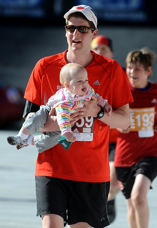 BOLDER116.JPG BOLDER<br /> Doug Vincent of Erie crosses the finish line with daughter Grace, 11 months, after taking her from his wife's arms in the stadium during the 32nd Annual Day Bolder Boulder on Monday.<br /> Photo by Marty Caivano/Camera/May 31, 2010