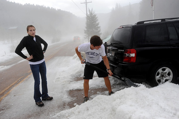 """HAIL.JPG HAIL<br /> Renee Anderson, left, and Greg Flood, visiting from Tulsa, Okla., dig a path for their car through piles of hail that fell on the town of Eldora, just outside Nederland, on Wednesday afternoon. A reported eight inches of hail fell, causing cars to get stuck and requiring a grader to clear the road. <br /> For a video of the storm aftermath, see  <a href=""""http://www.dailycamera.com"""">http://www.dailycamera.com</a>.<br /> Photo by Marty Caivano/Camera/July 28, 2010"""