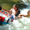 TUBING.JPG TUBING<br /> David Phelps, left, and Whit Boucher of Boulder capsize their double tube on a rapid in Boulder Creek near Eben G. Fine Park on Wednesday. <br /> Photo by Marty Caivano/Camera/June 29, 2010