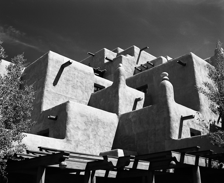 A modern New Mexico building constructed in a traditional pueblo style with adobe walls and square corners. (Scanned from black and white film.)