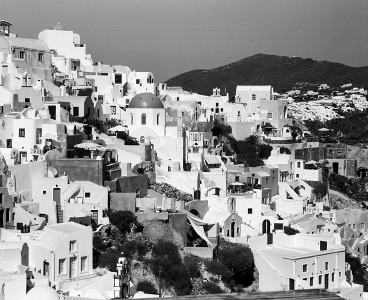 A view of the town of Oia on the Greek island of Santorini. The city snakes along the top of the hill which is the rim of an old crater. (Scanned from black and white film.)