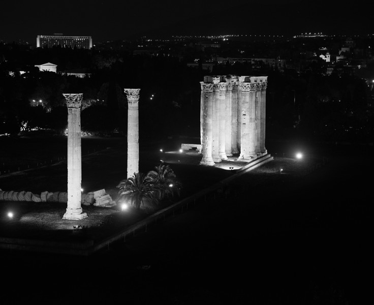 The temple of Zeus in Athens as viewed from above at night. The old columns are brightly illuminated while the rest of the city sparkles a little. (Scanned from black and white film.)