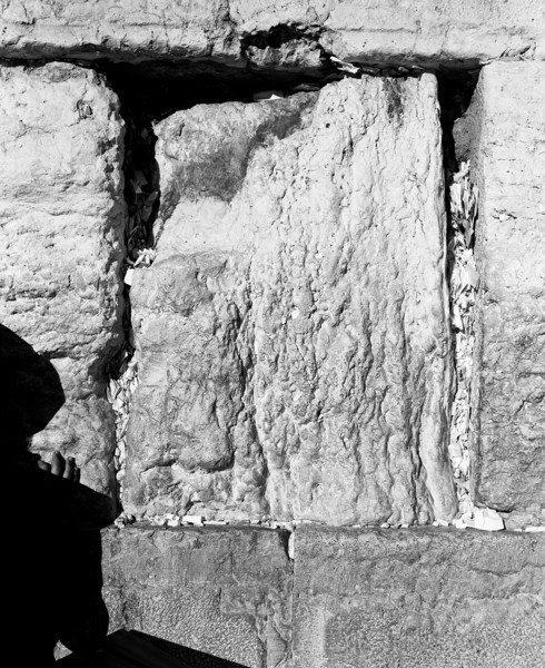 The shadow of a man with one hand touching the stones of the Western Wall in the afternoon before the start of Shabbat. The cracks in the wall are stuffed with small pieces of paper written with people's prayers.