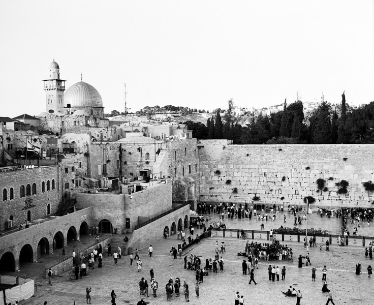In Jerusalem, as sundown approaches on Shabbat, the plaza at the Western Wall becomes crowded with people. The Dome of the Rock and a minaret are visible in the upper left. (Scanned from black and white film.)