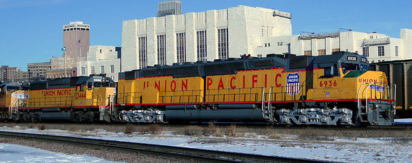 """Union Station, downtown Omaha, Nebraska. """"Once in twenty years"""" is what I call this stroke of luck as I caught the Union Pacific's (heritage fleet) No. 6936, its last operational EMD DDA40X locomotive (delivered approx. 1970), pulling a manifest train.  At 6,600 hp, this is one powerful locomotive. During occasional train chasing excursions, I leave luck to the draw and this particular day, I drew a straight flush.  The sound of this engine is distinctly different from normal locomotives and as the engine pulled out from the shadows beneath the bridge, I knew it was going to be a terrific shot. East bound trains come out from under the Tenth Street Bridge without announcement, as they head for the Missouri River Bridge, usually at 25 mph. On this occasion, fortune smiled upon me as I had barely just arrived."""