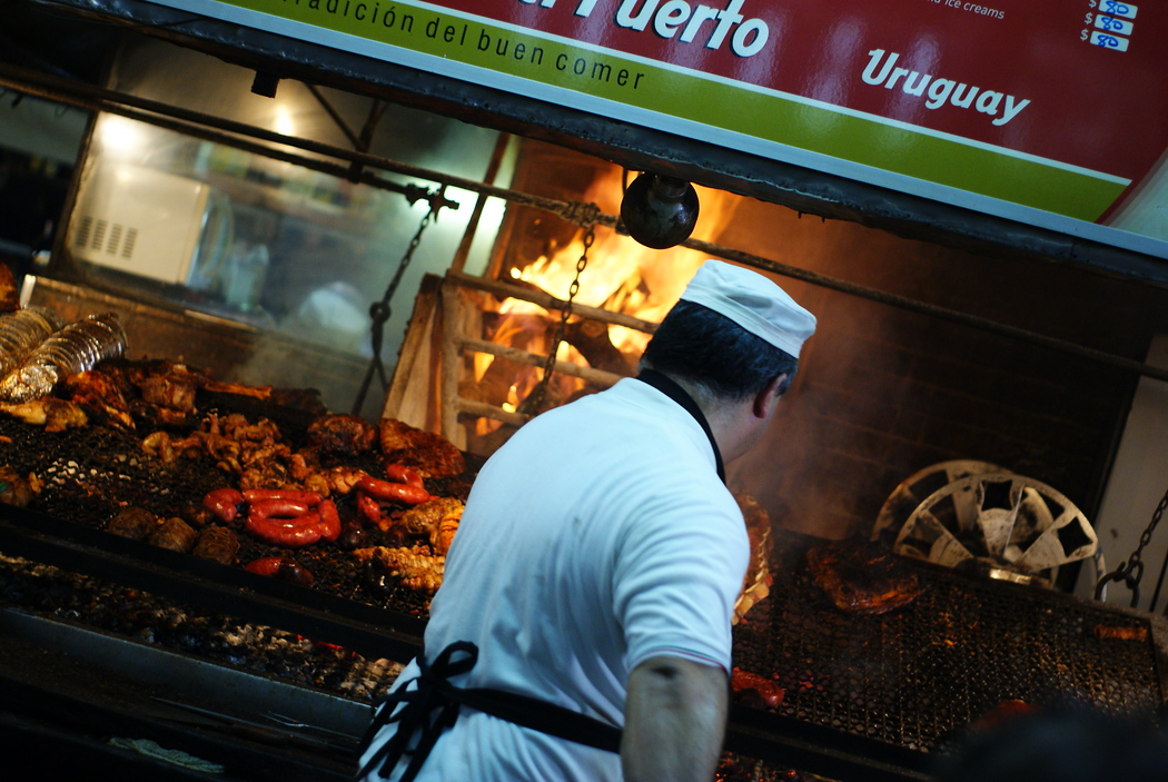 A Uruguayan cook barbecues an assortment of different meats on a large open grill - Montevideo, Uruguay.  Travel photo from Montevideo, Uruguay.