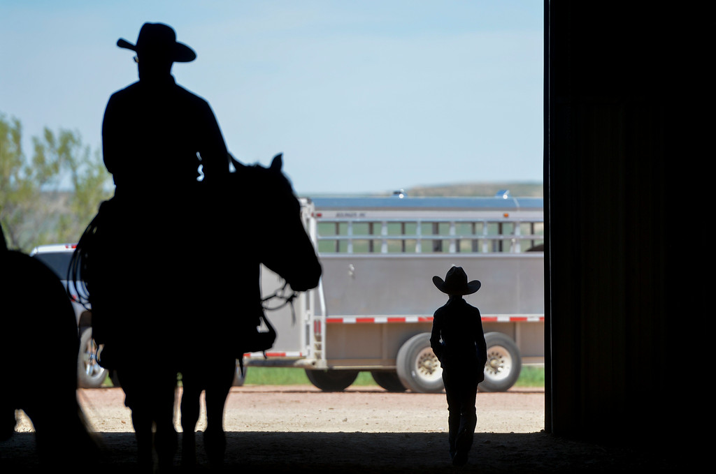 Justin Sheely | The Sheridan Press<br /> Competitors walk by the bay door during the Showdown in Sheridan cutting horse show Friday at the Sheridan College AgriPark in north Sheridan.