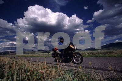 Rider on a BMW motorcycle riding through the Grand Tetons, WY after a severe thunderstorm