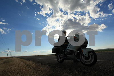 BMW rider parked along the highway with big clouds overhead, southeast WA state.