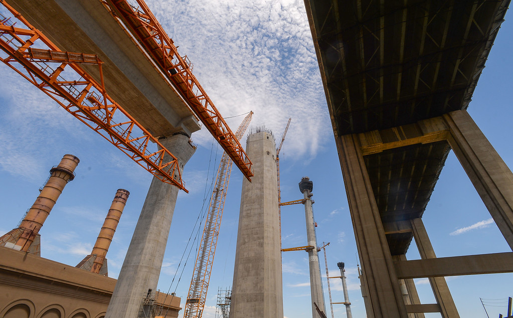 . The current Gerald Desmond Bridge, right, passes by the construction of its replacement. Construction crews spent the day slowly raising a giant orange colored scaffolding system into place to build the eastbound roadway of the new Gerald Desmond Bridge in Long Beach on Tuesday, August 1, 2017. The 3.1-million pound platform was slowly lifted into place on two bridge support columns. The scaffolding recently completed 3,000-foot segment of the westbound lanes and was moved to begin building the eastbound lanes. (Photo by Scott Varley, Press-Telegram/SCNG)