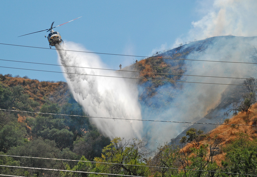 . An LA County FD helicopter makes a water drop on a hot spot during a 29 acre brush fire in Towsley canyon in the Newhall Pass this afternoon.   (Photo by Mike Meadows)