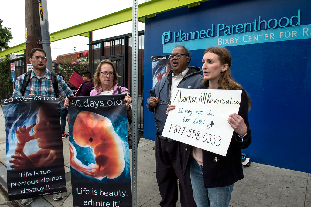 . Lisa Ebiner Gavit, right, Christopher Davis, and others gather as they continue praying the Rosary during a Pro-Life Prayer Vigil at Planned Parenthood Bixby Center for Reproductive Health in Los Angeles on Saturday, February 11, 2017. (Photo by Ed Crisostomo, Los Angeles Daily News/SCNG)