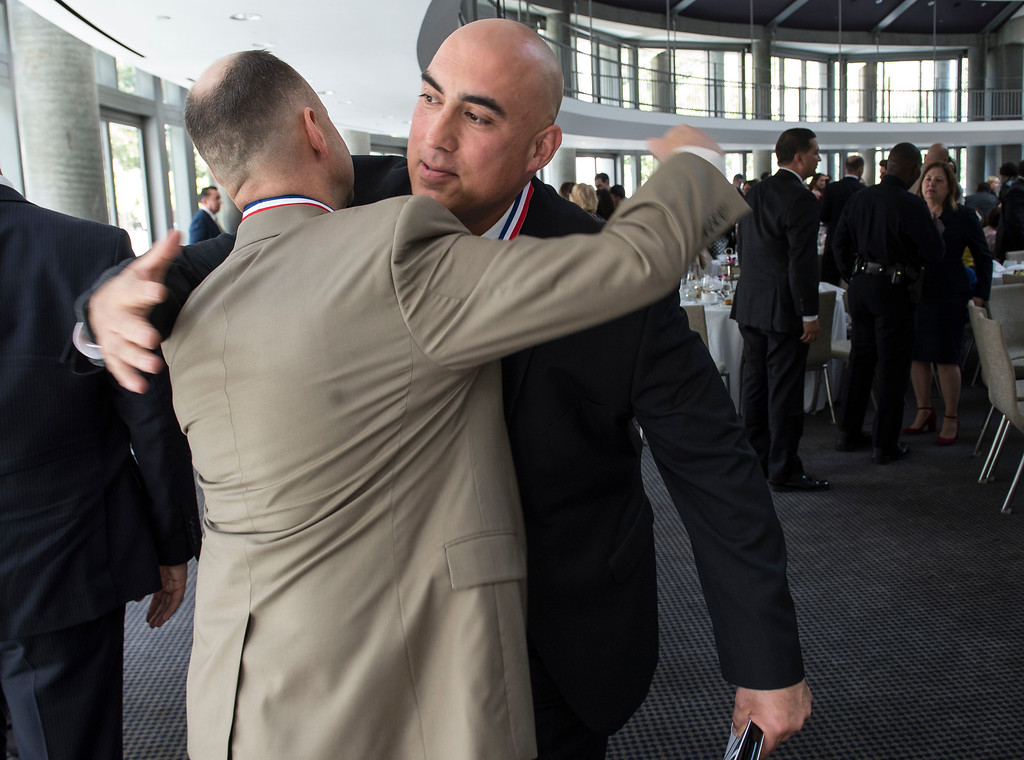 . LAPD Detectives Carter Fenstemacher, left, and Richard Lozano embrace during an awards ceremony, law enforcement personnel to be honored for combating hate and bigotry, at Skirball Cultural Center in Los Angeles on Tuesday, March 14, 2017. The two are honorees for the San Fernando Valley Peckerwoods Takedown. (Photo by Ed Crisostomo, Los Angeles Daily News/SCNG)
