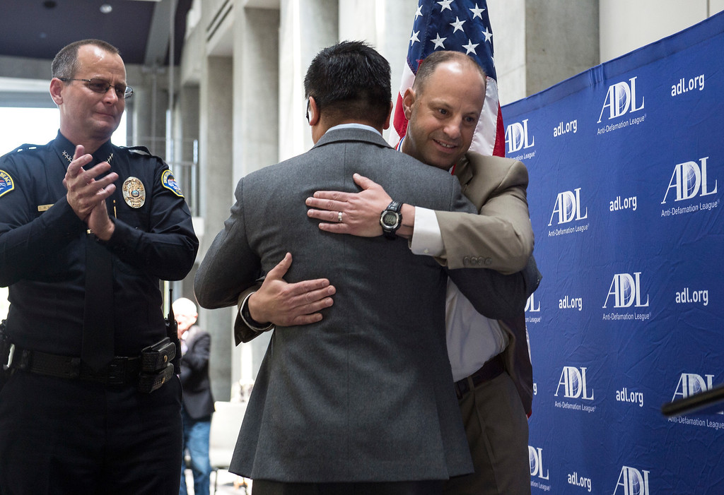 . LAPD Detective Carter Fenstemacher, right, one of the honorees for the San Fernando Valley Peckerwoods Takedown, embraces Anh Truong, assistant supervising deputy city attorney, as Huntington Beach Police Chief Robert Handy looks on during an awards ceremony, law enforcement personnel to be honored for combating hate and bigotry, at Skirball Cultural Center in Los Angeles on Tuesday, March 14, 2017. (Photo by Ed Crisostomo, Los Angeles Daily News/SCNG)