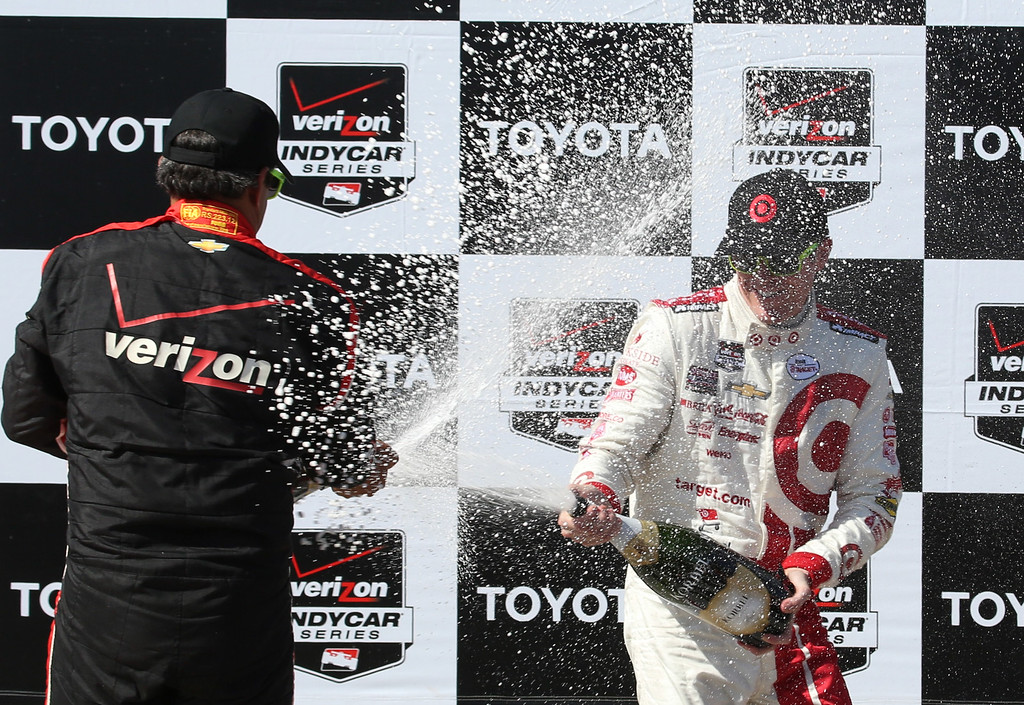 . Juan Pablo Montoya, left gives a champagne shower to Scott Dixon the winner of the 41st Toyota Grand Prix of Long Beach Sunday, April 19th, 2015. Chuck Bennett/Staff Photographer