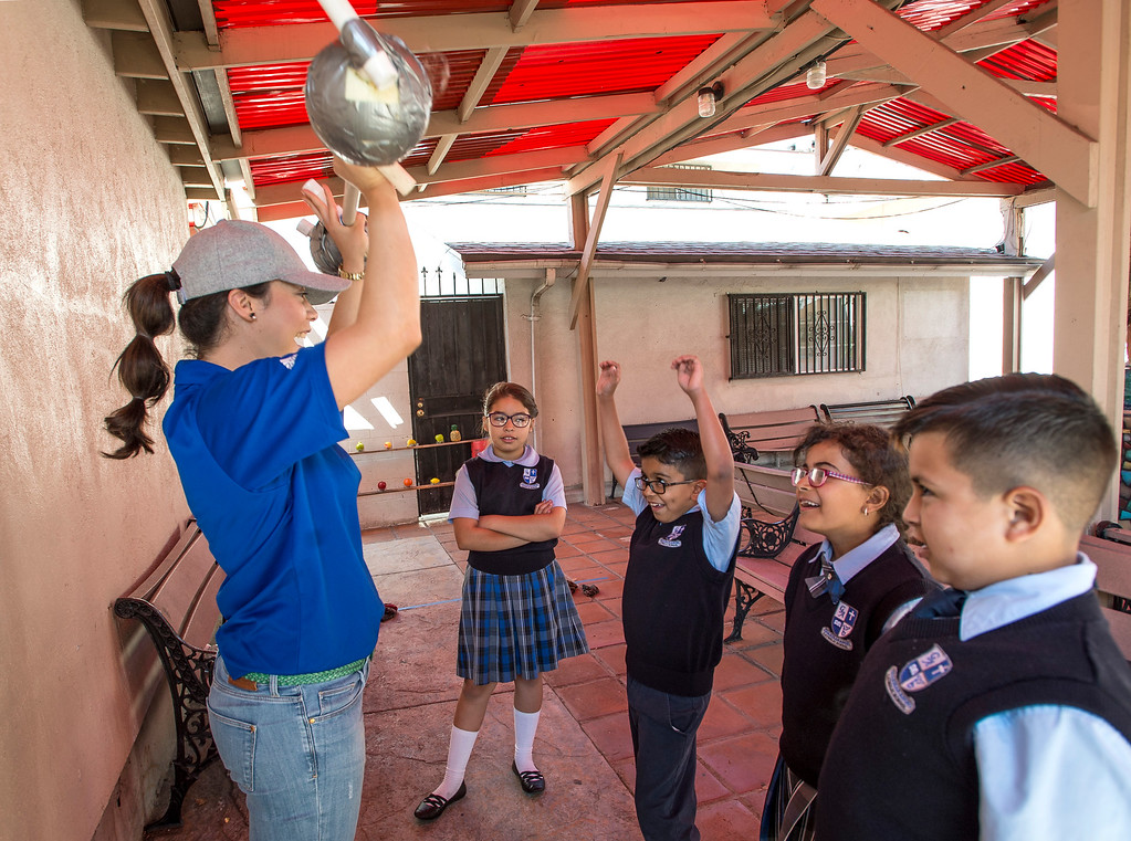 . Third-graders Jandarene Garcia, 9, from left, Omar Rangel, 9, Jessica Salib, 9, and DJ Gonzalez, 8, react as Melissa Mendoza, M.S., Providence Health & Services, lifts a bar with a watermelon on each side during the Nutrition Olympics for kids in grades 1-4 at Guardian Angel School in Pacoima on Friday, June 09, 2017. According to Lauren Lewow, external communication specialist, we�re honored to work with Guardian Angel School to bring programming like this nutrition Olympics to local communities served by Providence Health & Services. In 2016, Providence Health & Services spent $25 million on community health care and education programs, including charity care and wellness programming for the San Fernando Valley, Westside and South Bay including the Providence Community Health Wellness and Activity Center in Wilmington and the tattoo removal program in the Valley. (Photo by Ed Crisostomo, Los Angeles Daily News/SCNG)