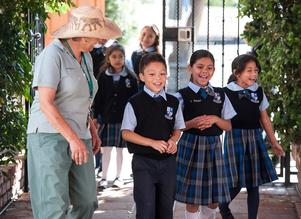 . Second-graders Walter Villeda, 8, from left,  Audrina Rangel, 7, and Jessica Gomez, 7, enter as Suzanna Wood, R.N., Providence Health & Services, leads the way during the Nutrition Olympics for kids in grades 1-4 at Guardian Angel School in Pacoima on Friday, June 09, 2017. According to Lauren Lewow, external communication specialist, we�re honored to work with Guardian Angel School to bring programming like this nutrition Olympics to local communities served by Providence Health & Services. In 2016, Providence Health & Services spent $25 million on community health care and education programs, including charity care and wellness programming for the San Fernando Valley, Westside and South Bay including the Providence Community Health Wellness and Activity Center in Wilmington and the tattoo removal program in the Valley. (Photo by Ed Crisostomo, Los Angeles Daily News/SCNG)