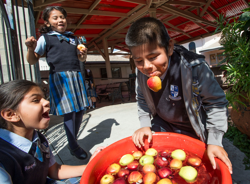 . Second-graders Audrina Rangel, 7, left, and Jessica Gomez, 7, cheer as Steven Perez, 8, grabs an apple without using his hand during the Nutrition Olympics for kids in grades 1-4 at Guardian Angel School in Pacoima on Friday, June 09, 2017. According to Lauren Lewow, external communication specialist, we�re honored to work with Guardian Angel School to bring programming like this nutrition Olympics to local communities served by Providence Health & Services. In 2016, Providence Health & Services spent $25 million on community health care and education programs, including charity care and wellness programming for the San Fernando Valley, Westside and South Bay including the Providence Community Health Wellness and Activity Center in Wilmington and the tattoo removal program in the Valley. (Photo by Ed Crisostomo, Los Angeles Daily News/SCNG)