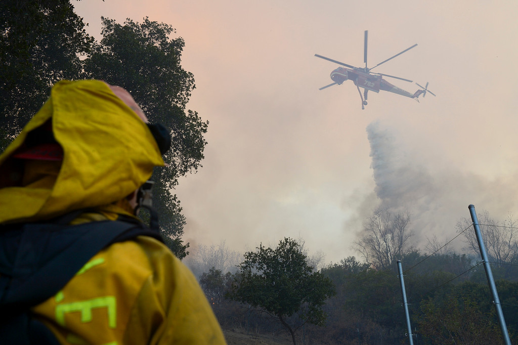. A firefighter looks on as a helicopter makes a drop to protect homes near Placerita Canyon road and Sand Canyon road Sunday.   More than 15 structures have been destroyed in the fire which has consumed more than 22,000 acres so far with 10% containment.  (Photo by David Crane Southern California News Group)