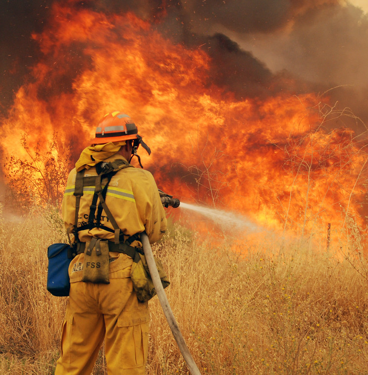 . Santa Clarita, Ca  A LA County firefighter ffghts fire along Placerita Canyon Road. (Photo by Mike Meadows)