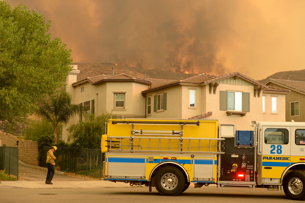 . Structure protection fire engines move in to protect homes near Via Princessa in Santa Clarita Sunday.   More than 15 structures have been destroyed in the fire which has consumed more than 22,000 acres so far with 10% containment.  (Photo by David Crane Southern California News Group)