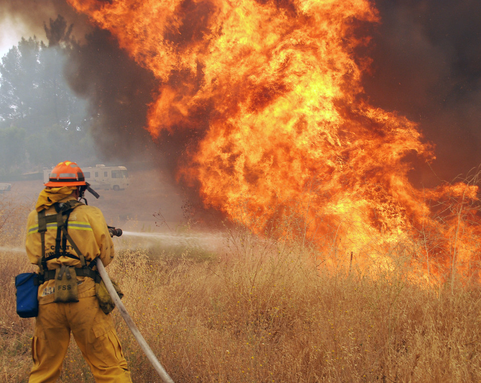 . Santa Clarita, Ca  An LA County firefighter feels the heat as huge flames roar along Placerita Canyon Road this afternoon. The entire canyon is in dire danger of being burned out. (Photo by Mike Meadows)