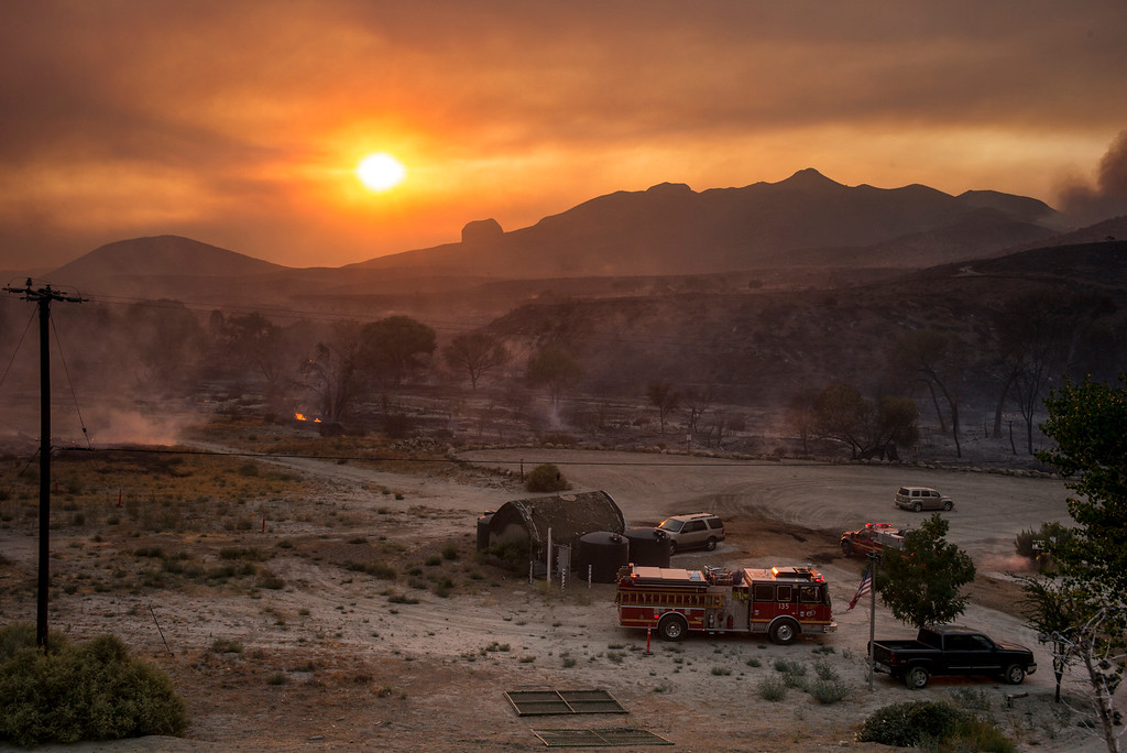 . Firefighters watch for hot spots after a path of fire rolled though this area along Soledad Canyon road in Action Sunday.    More than 15 structures have been destroyed in the fire which has consumed more than 22,000 acres so far with 10% containment.  (Photo by David Crane Southern California News Group)