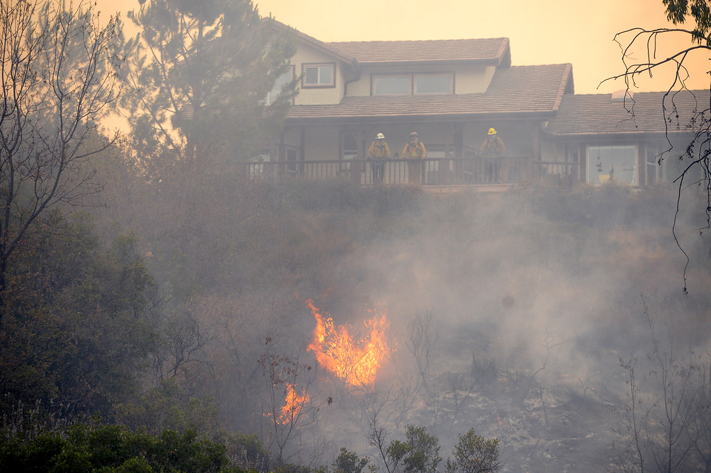 . Fire comes very close to a home along Placerita Canyon road Sunday.   More than 15 structures have been destroyed in the fire which has consumed more than 22,000 acres so far with 10% containment.  (Photo by David Crane Southern California News Group)