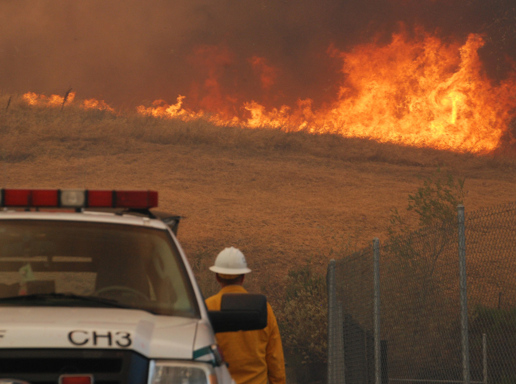 . Santa Clariya, Ca  An Forest Service Chief can only watch as flame roar across grass and brush just off Placerita canyon Road this afternoon.(Photo by Mike Meadows)