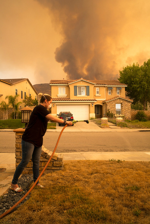 . Kaylee Bardin soaks her lawn as flames approach her house in the Fairoaks neighborhood near Via Princessa in Santa Clarita Sunday.   More than 15 structures have been destroyed in the fire which has consumed more than 22,000 acres so far with 10% containment.  (Photo by David Crane Southern California News Group)