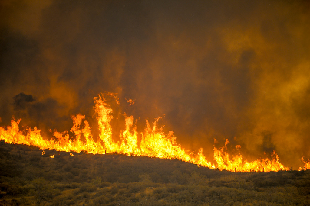 . Flames roar across a ridge near Via Princessa in Santa Clarita Sunday.   More than 15 structures have been destroyed in the fire which has consumed more than 22,000 acres so far with 10% containment.  (Photo by David Crane Southern California News Group)