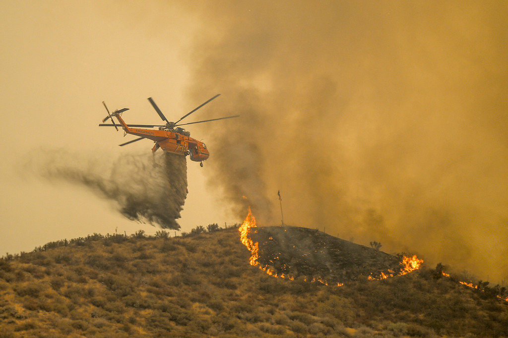 . A helicopter makes a drop above homes near Via Princessa in Santa Clarita Sunday.   More than 15 structures have been destroyed in the fire which has consumed more than 22,000 acres so far with 10% containment.  (Photo by David Crane Southern California News Group)