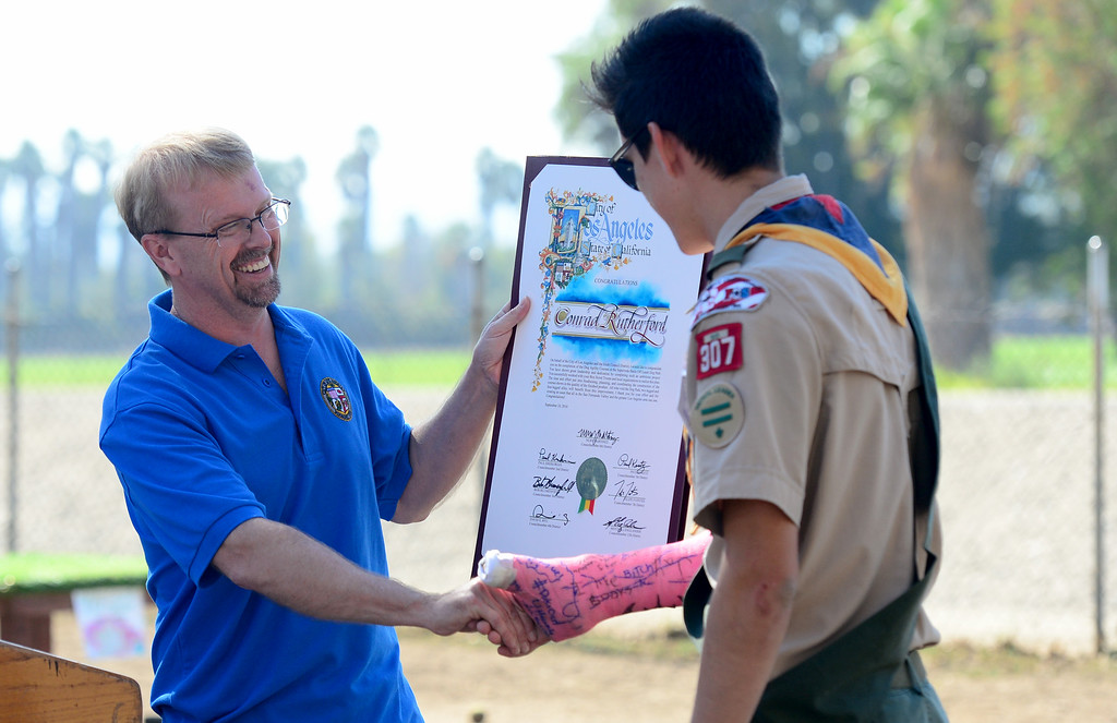 . Michael A. Shull, General Manager of Los Angeles Department of Recreation and Parks,  congratulates Conrad Rutherford.  Eagle Scout Conrad Rutherford raised funds to design and build three canine agility courses this summer at the Sepulveda Basin Off-Leash Dog Park. On Saturday, September 10, 2016, city and parks officials dedicated the courses that have delighted dog owners and put the pooches through the hoops.  (Photo by Dean Musgrove, Los Angeles Daily News/SCNG)