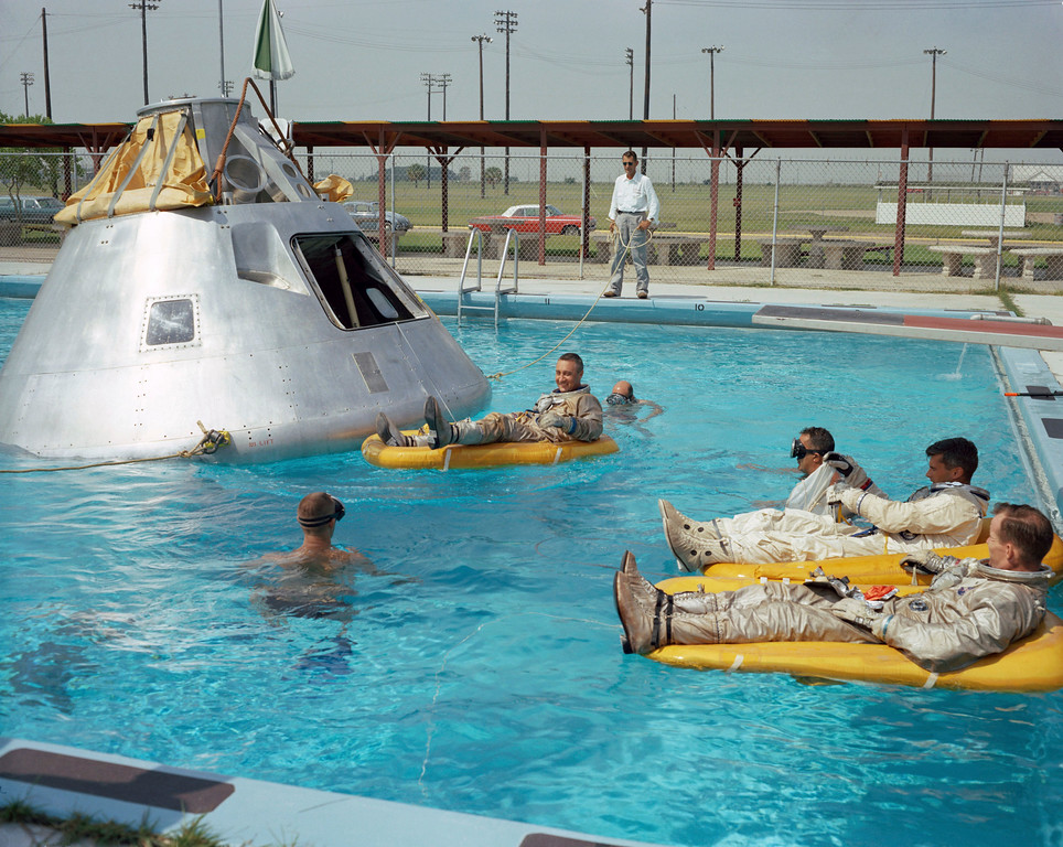 . In this June 1966 photo made available by NASA, the Apollo 1 crew practices water evacuation procedures with a full scale model of the spacecraft at Ellington AFB, near the then-Manned Spacecraft Center, Houston. In the rafts at right are astronauts Ed White and Roger Chaffee, foreground. In a raft near the spacecraft is astronaut Virgil Grissom. (NASA via AP)