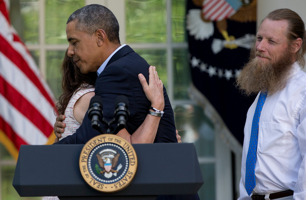 . President Barack Obama hugs Jani Bergdahl, as Bob Bergdahl, stands at right, during a news conference in the Rose Garden of the White House in Washington, Saturday, May 31, 2014 about the release of their son, U.S. Army Sgt. Bowe Bergdahl, from captivity. Bergdahl, 28, had been held prisoner by the Taliban since June 30, 2009. He was handed over to U.S. special forces by the Taliban in exchange for the release of five Afghan detainees held by the United States. (AP Photo/Carolyn Kaster)